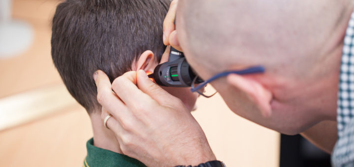 Examining the ear with an otoscope.