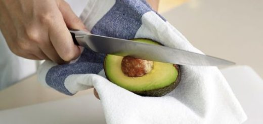 Hand using knife to get rid off avocado seed